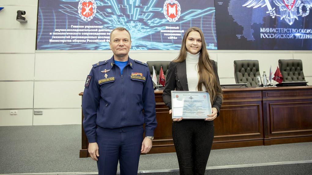 Доктор военных наук генерал-майор Андрей Гончаров вручает награду студентке Елене Юзько.