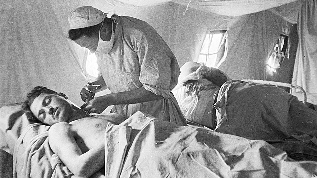 Врачи оперируют раненного солдата.