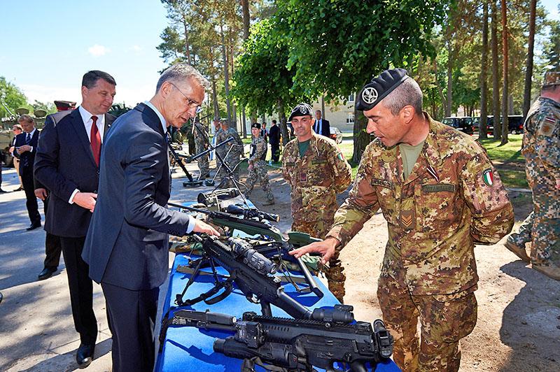 Президент Латвии Раймонд Вейонис и Йенс Столтенберг осматривают оружие итальянских военных.