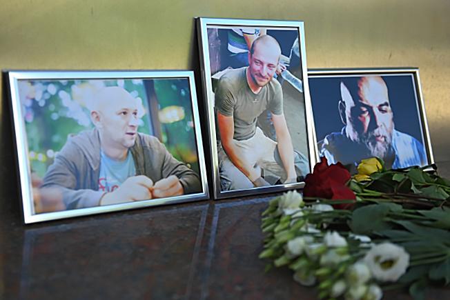 Цветы у фотографий погибших в Центральноафриканской Республике журналистов: Орхана Джемаля, Кирилла Радченко и Александра Расторгуева (справа налево) возле Дома журналистов в Москве.