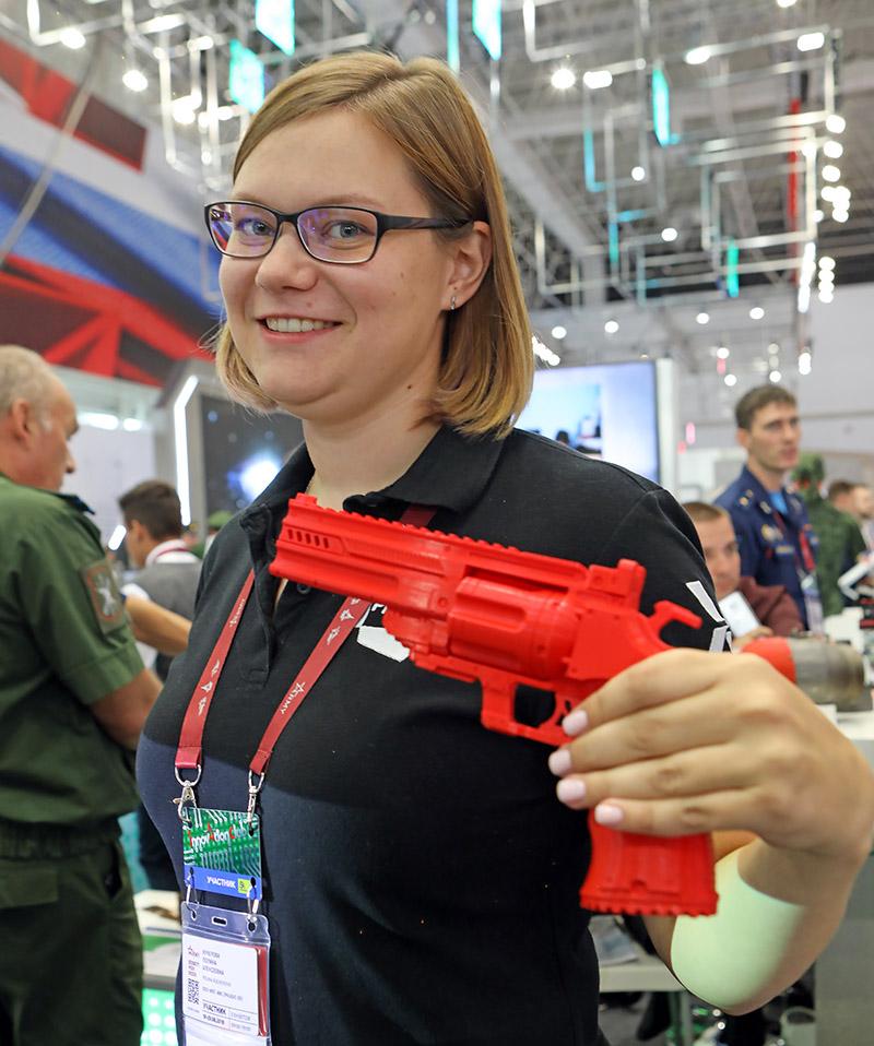Полина Кучерова из компании PICASO 3D показывает распечатанный на принтере красный револьвер.