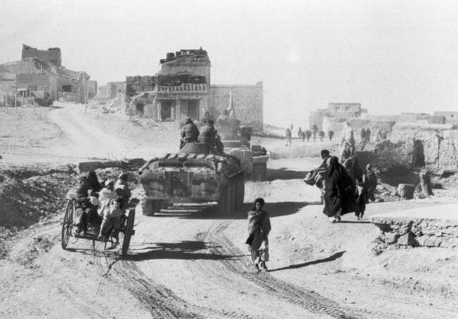 Советская военная техника едет по улице кишлака в Афганистане.