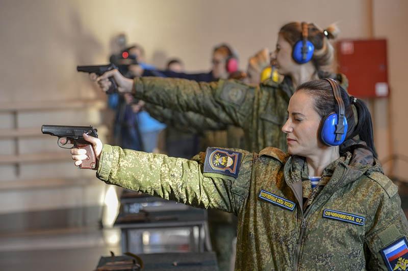 Девушки отрабытывают навыки стрельбы из пистолета.