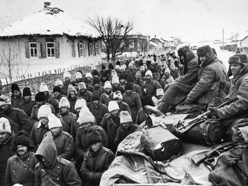 Колонна румынских солдат, захваченных под Сталинградом, движется мимо грузовика с красноармейцами.