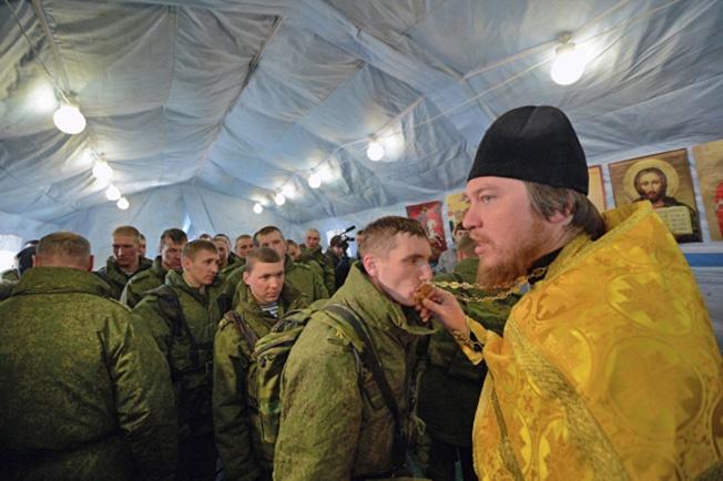 Главный военный священник отец Михаил проводит службу в мобильном храме.