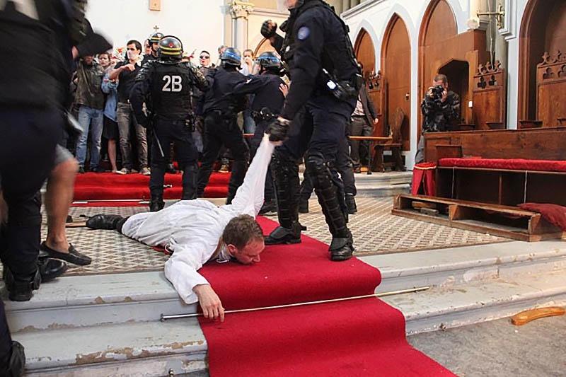 Полиция выволакивает священника из церкви Святой Риты в Париже.