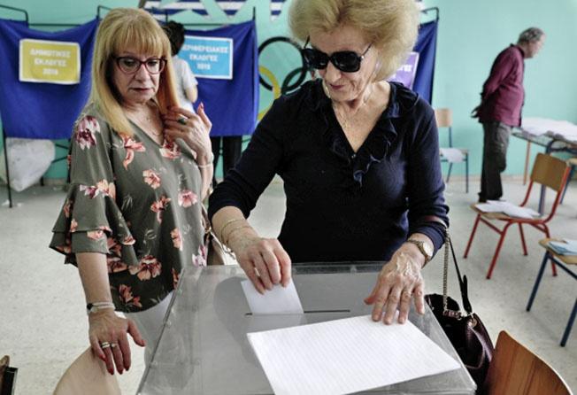 Избиратели во время голосования на выборах в Европейский парламент (ЕП) на одном из избирательных участков в Афинах.