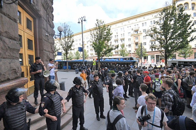 Участники несанкционированной акции в поддержку кандидатов в депутаты Мосгордумы и полиция у здания мэрии Москвы.