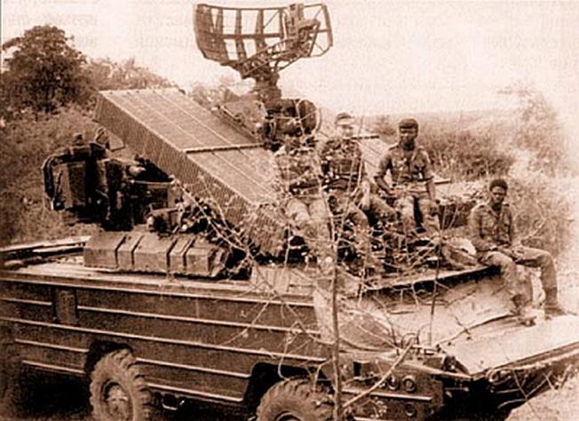 На броне боевой машины ПВО «ОСА-АК» инженер Брянского автозавода А. Павлов (второй слева). Снимок сделан после успешного отражения налёта южноафриканской авиации на позиции ФАПЛА. Район Риу-де-Арея и Шибембы, 1985 г.
