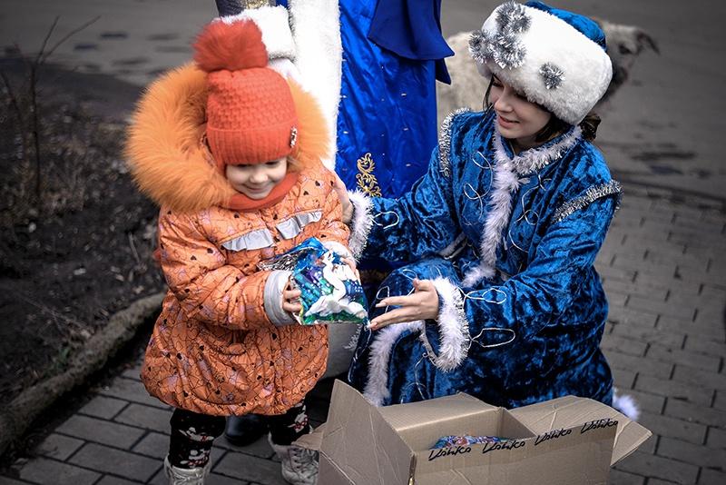 Снегурочка в прифронтовом районе раздает подарки.
