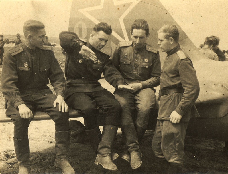 Командир эскадрильи А. Лебедев (второй слева) проводит разбор полётов.