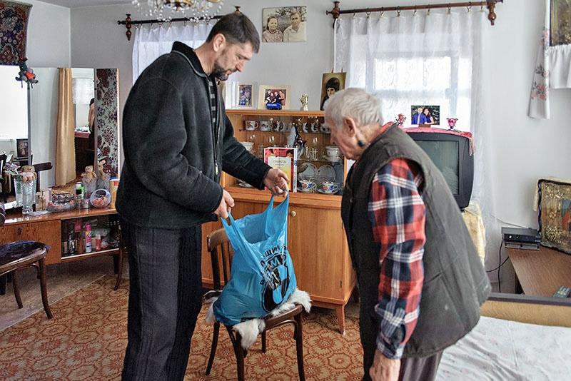 Константин Чалый передаёт продуктовый набор ветерану ВОВ Ф.И. Кузьменко.