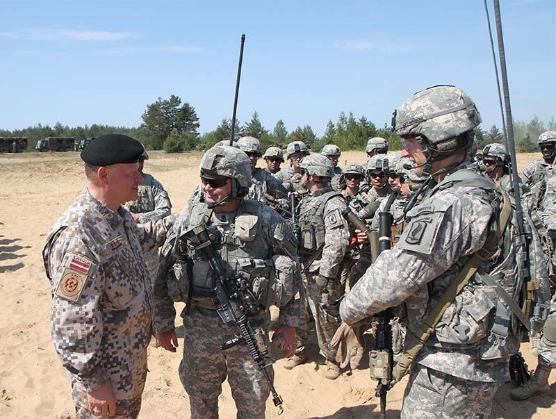 Генерал-лейтенант Раймондс Граубе беседует с десантниками армии США из 1-го батальона 503-го пехотного полка 173-й воздушно-десантной бригады в военном лагере Адажи, Латвия.