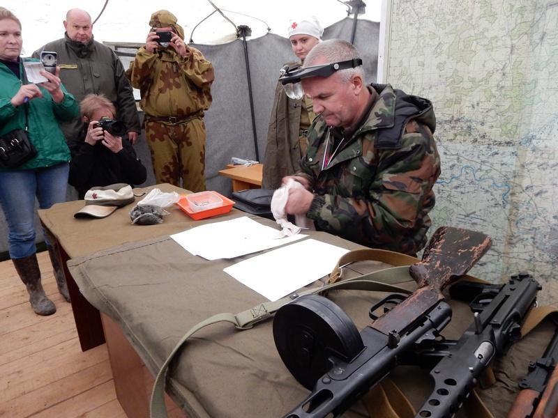 Процесс извлечения записки из медальона погибшего советского воина под Ржевом, в палатке лагеря поисковиков.