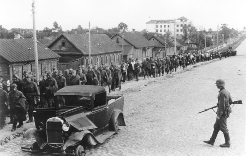 Колонна советских военнопленных и разбитый автомобиль ГАЗ-4 на улицах Минска. 2 июля 1941 года.