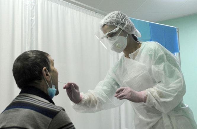 Медицинская сестра берёт мазок у пациента для ПЦР-теста на коронавирус COVID-19.