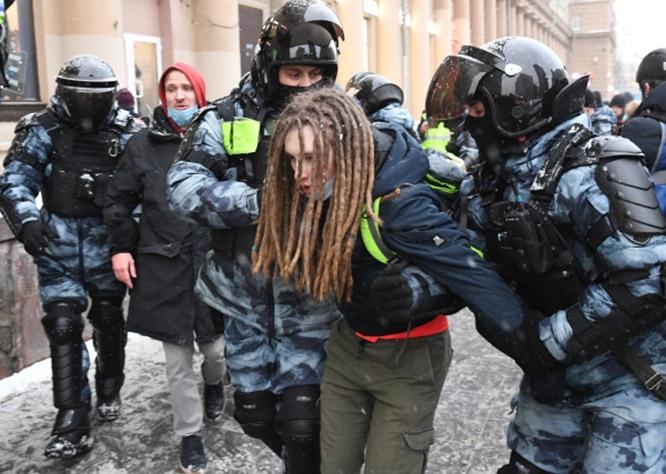 Сотрудники правоохранительных органов задерживают участника несанкционированной акции сторонников Алексея Навального в Москве 31 января.