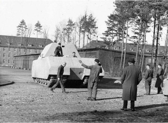 Немецкий опытный сверхтяжёлый танк «Маус» во время ходовых испытаний на полигоне в городе Бёблинген. Спиной к зрителю в шляпе стоит конструктор танка Фердинанд Порше.