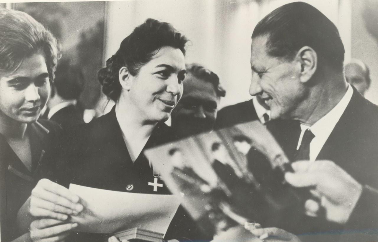 Посол Польши Э. Пщулковский (справа) поздравляет радистку А. Анисимову (вторая справа) с награждением её орденом «Партизанский Крест». 1964 год.