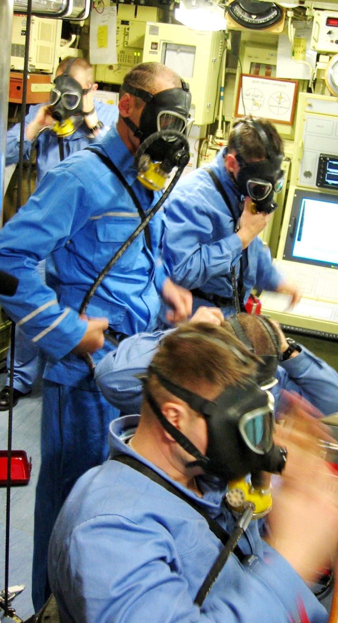 По вводной задымления отсека сам командир надевает маску СДС - стационарной дыхательной системы - и продолжает работать в ней, как и его подчинённые.