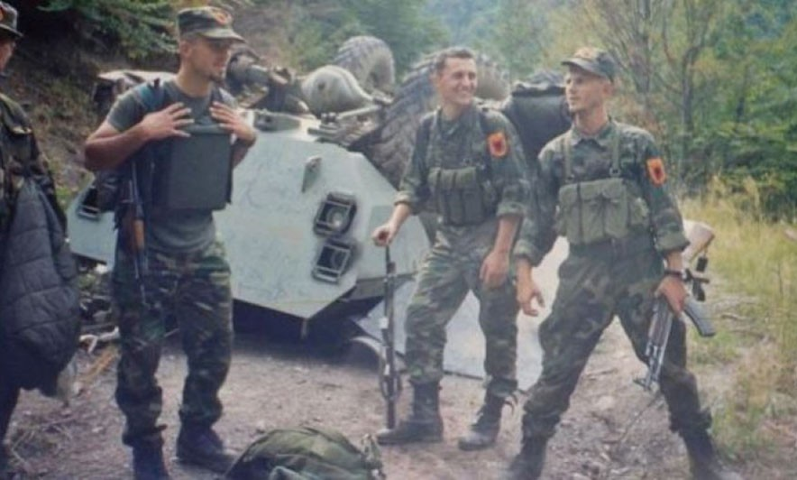 Боевики ОАК стоят рядом с уничтоженным сербским БТР.