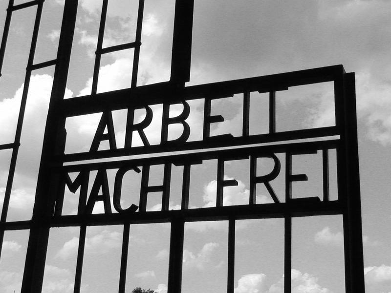 «Arbeit macht frei» («Труд делает свободным») - вывеска над воротами лагеря смерти Заксенхаузен, куда был переведён Девятаев с тремя другими участниками подкопа.