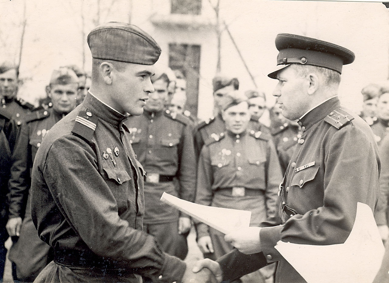 Командир десантного полка полковник Александр Лазаренко вручает грамоту отличившемуся сержанту.