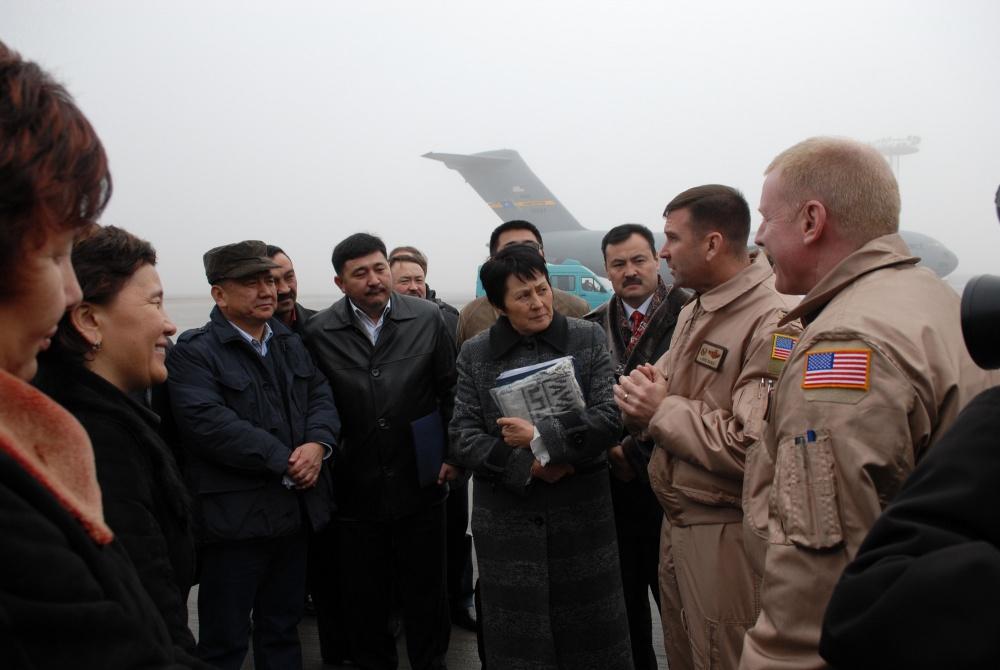 Командир 376-го авиационного экспедиционного крыла полковник Кристофер Бенс приветствует члена парламента Кыргызстана на брифинге миссии во время визита на авиабазе Манас.