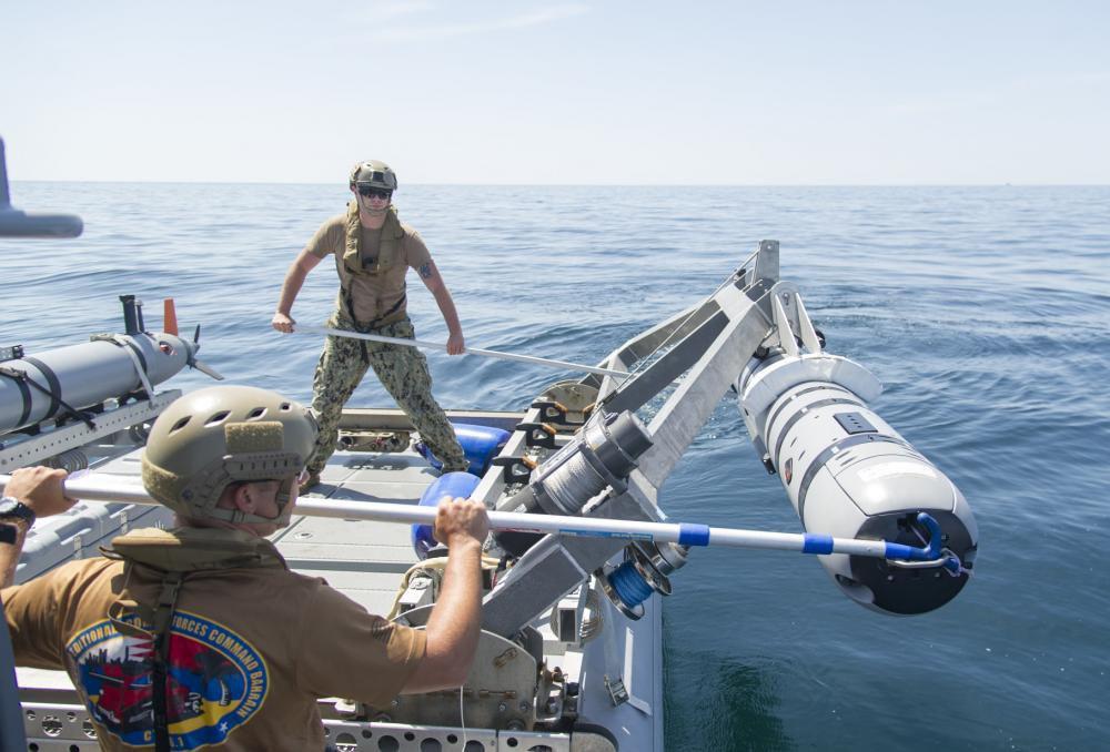 Моряки ВМС США опускают REMUS 600 в воду во время учений по противоминной защите.