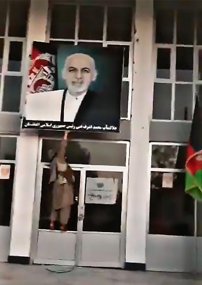 Талиб* срывает портрет бежавшего президента Ашрафа Гани в захваченном городе.