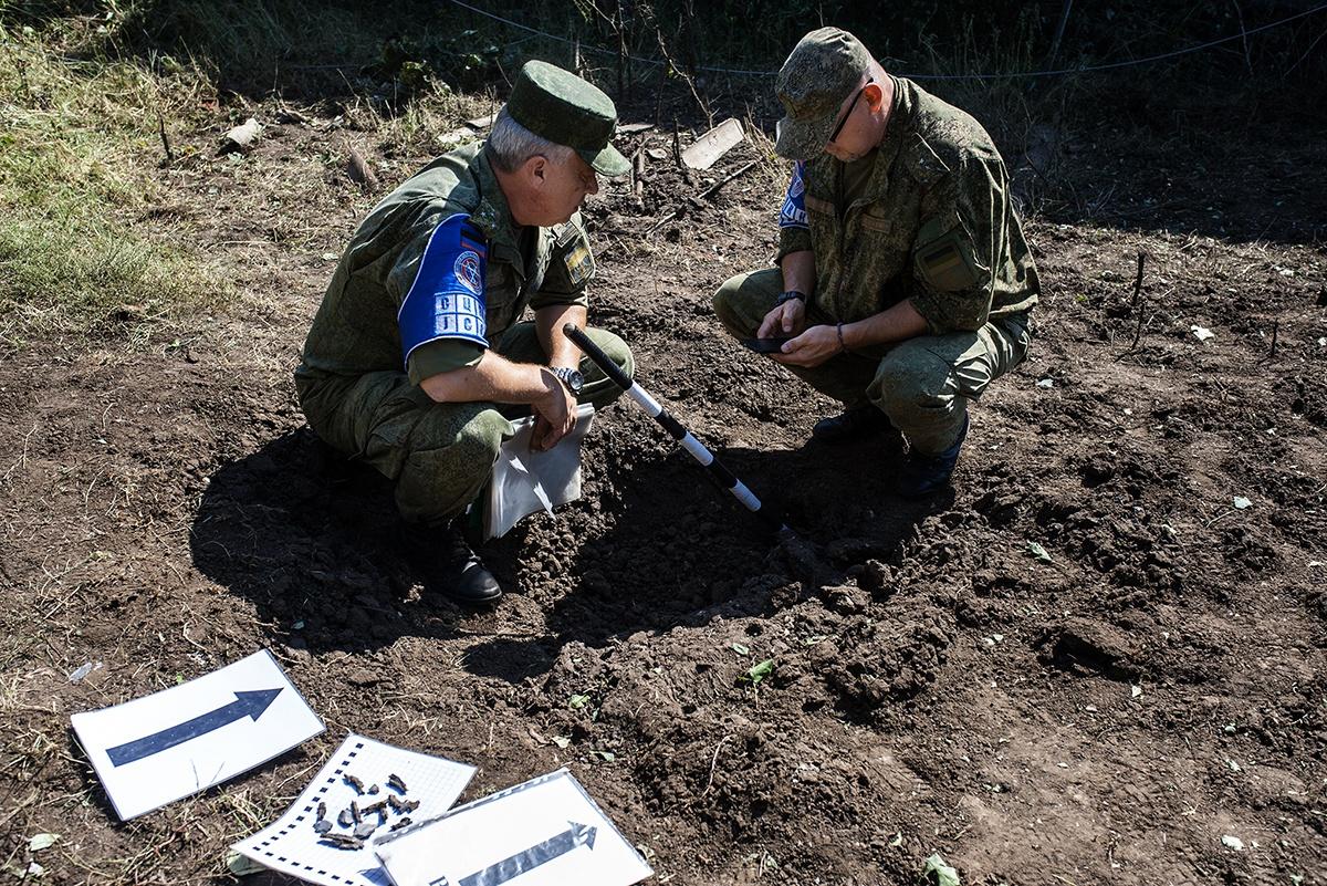 Представители Совместного центра по контролю и координации режима прекращения огня и стабилизации обстановки на юго-востоке Украины осматривают воронку на месте происшествия.