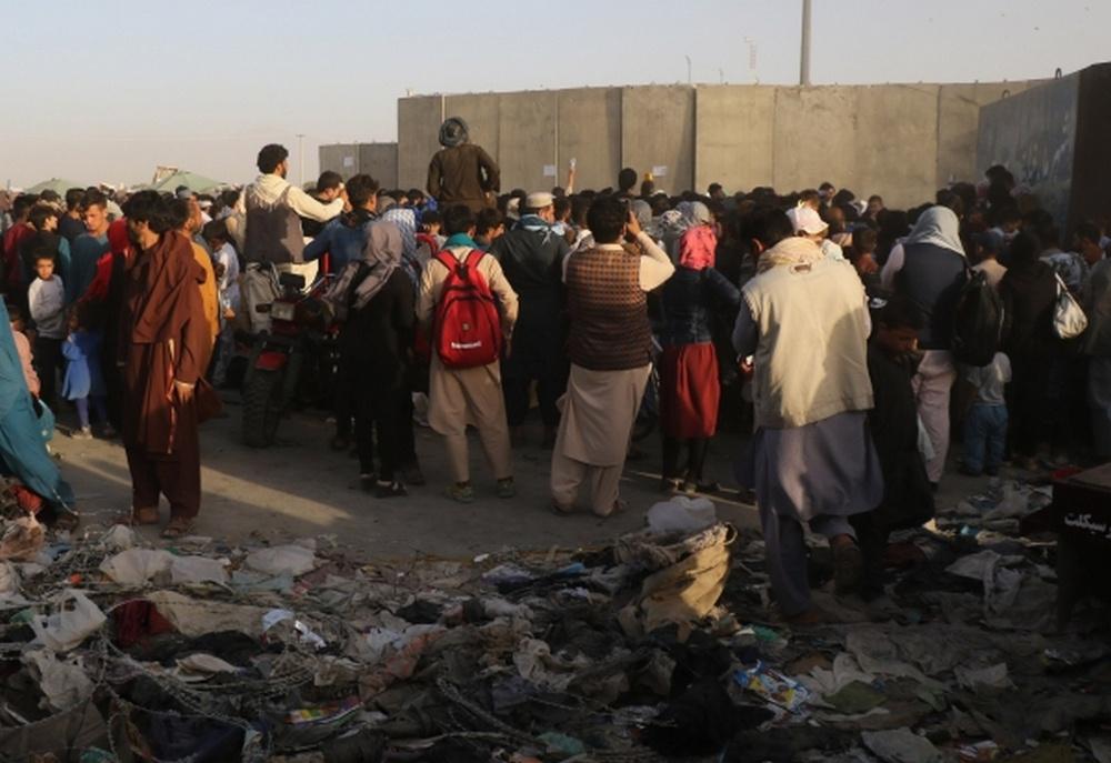 Люди возле пункта эвакуации возле международного аэропорта имени Хамида Карзая в Кабуле.