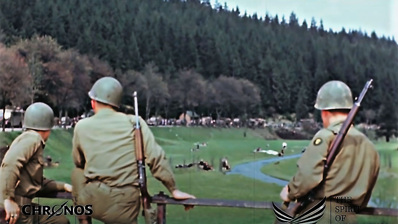 Американские солдаты наблюдают за приближающейся колонной немецких грузовиков с гитлеровцами.