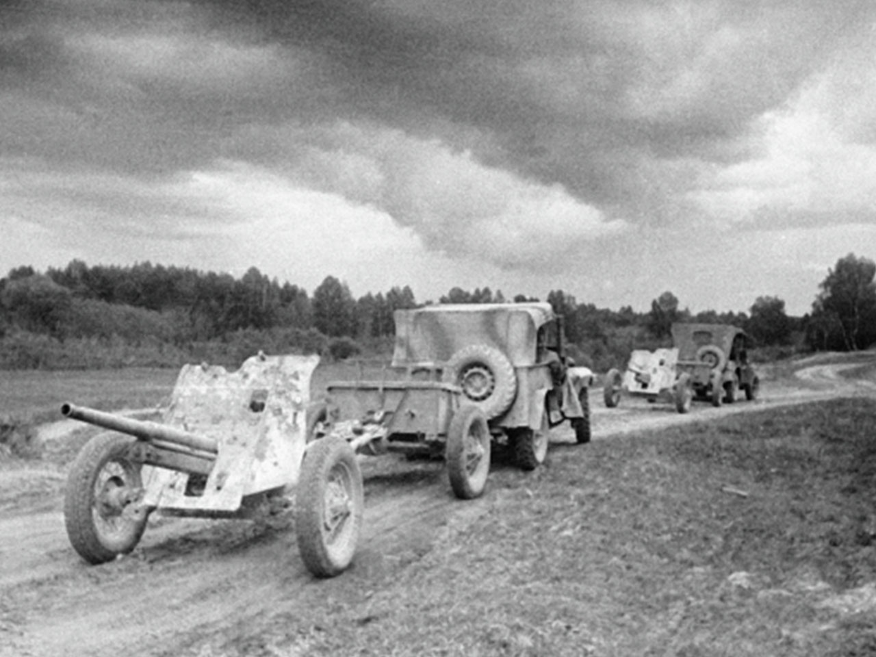 Машины ГАЗ-67 тянут по дороге артиллерийские орудия.