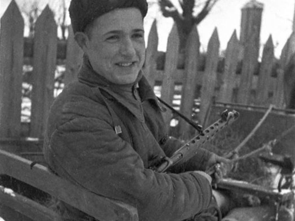 Молодой советский партизан в конных санях. Партизан вооружен пистолетом-пулеметом ППС-43.