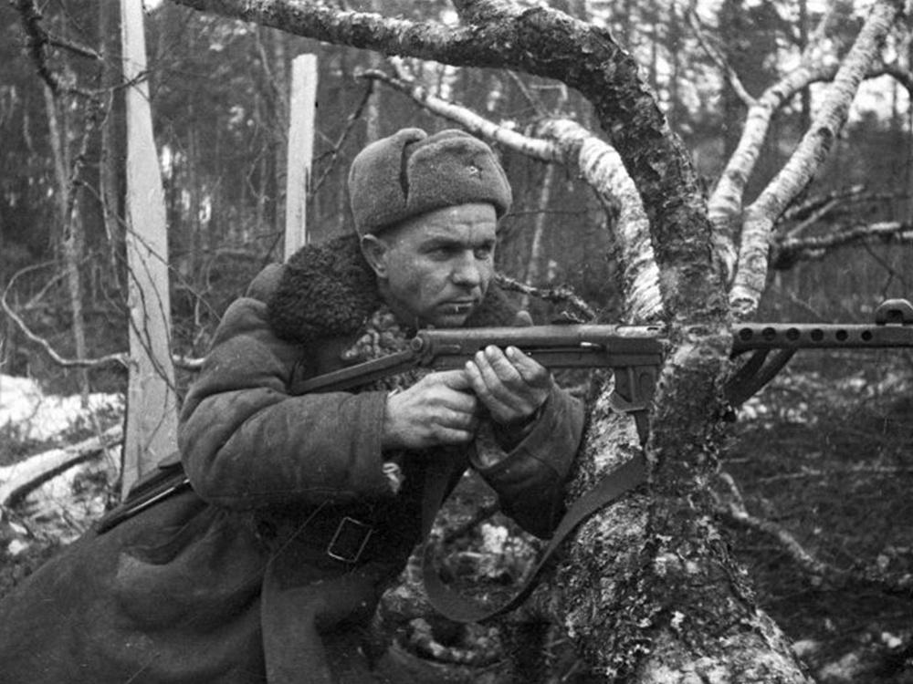 Офицер РККА, изготовившийся к стрельбе у поваленного дерева. Офицер вооружен пистолетом-пулеметом ППС-43