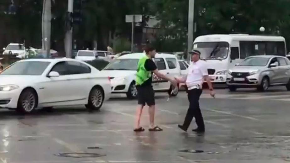 В Ростове прохожий регулировал дорожное движение при помощи зонтика: видео