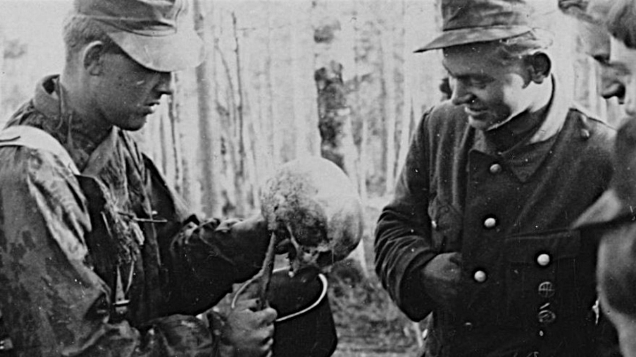 Норвежские эсэсовцы осматривают череп красноармейца<figcaption class=